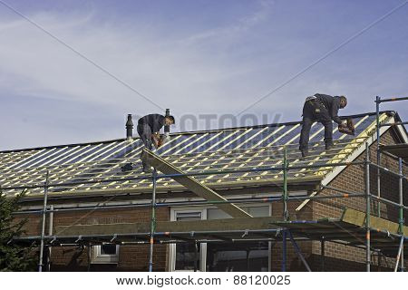Carpenters applying roof battens