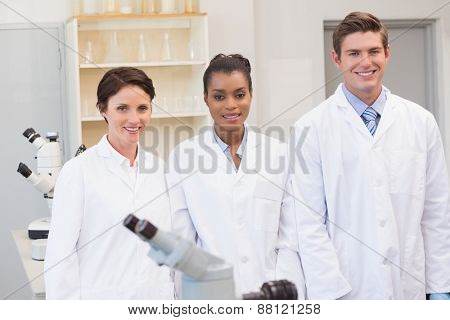 Smiling scientists team looking at camera in the laboratory