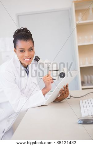 Smiling scientist looking at camera and taking notes in laboratory