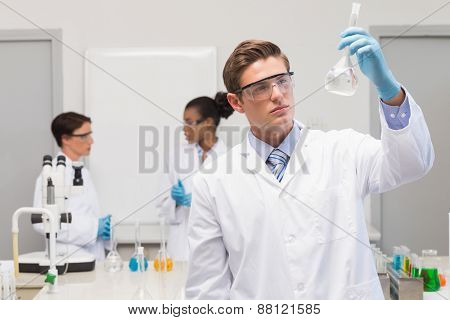 Scientist looking at white precipitate while colleagues talking together in the laboratory