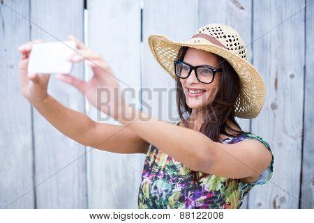 Smiling beautiful brunette taking selfie on wooden plank background