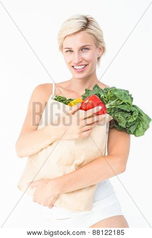 Attractive woman holding bag of vegetables on white background