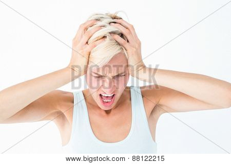 Angry blonde woman screaming and holding her head on white background
