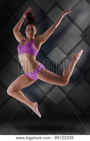 Fit brunette jumping and posing against dark grey room