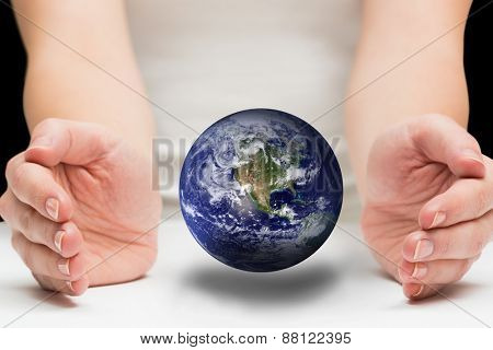 Hands presenting against earth