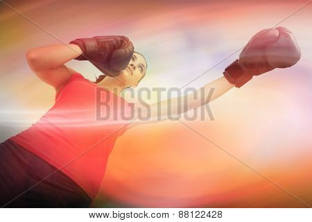 Fit woman boxing against purple and orange sky