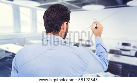 Businessman in suit writing with marker against classroom