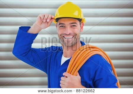 Confident repairman wearing hard hat while holding wire roll against grey shutters