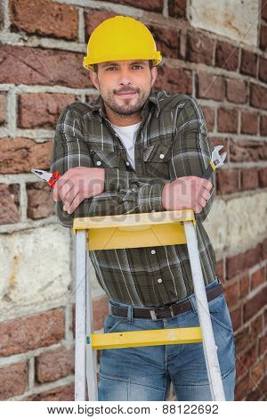 Manual worker against red brick wall