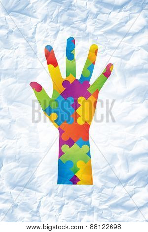 Autism awareness hand against crumpled white page