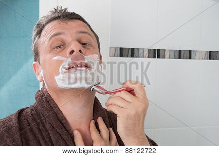 Man Shaving With A Razor Blade And Shaving Cream