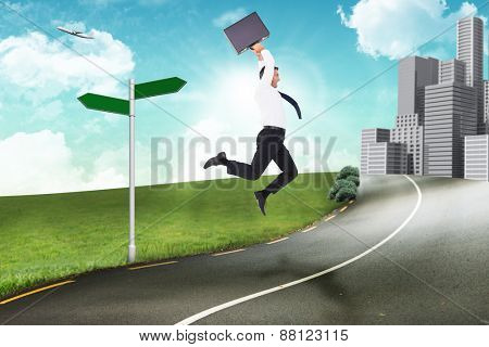 Smiling businessman leaping while briefcase against road leading out to the horizon