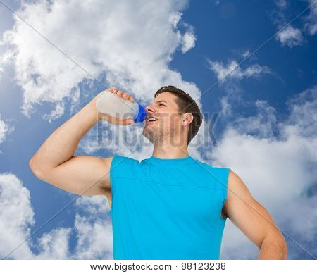 Smiling young man drinking water against bright blue sky with clouds