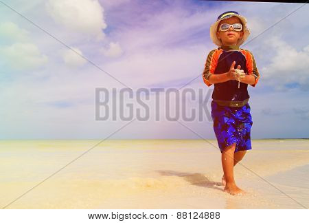 little boy playing on sand beach