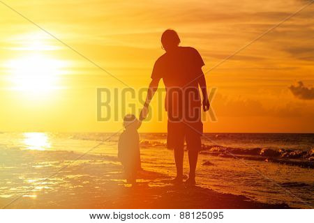 silhouettes of father and little daughter walking at sunset