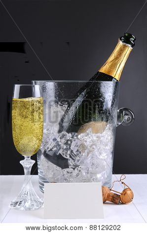 Closeup of a crystal champagne ice bucket and a full glass of bubbly. A blank table tent and cork in front of the open bottle lay on the white table cloth, over a light to dark background.