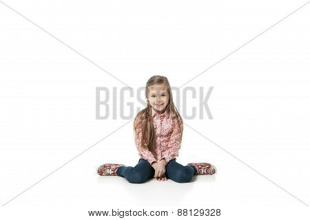 Pretty little girl sitting on the floor in jeans