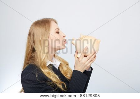 Businesswoman holding piggy bank.