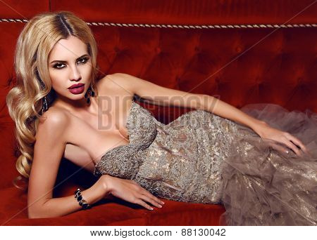 Gorgeous Woman With Blond Hair In Elegant Dress Lying On Red Div
