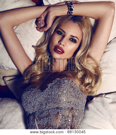 Gorgeous Woman With Blond Hair In Elegant Dress Lying On Divan
