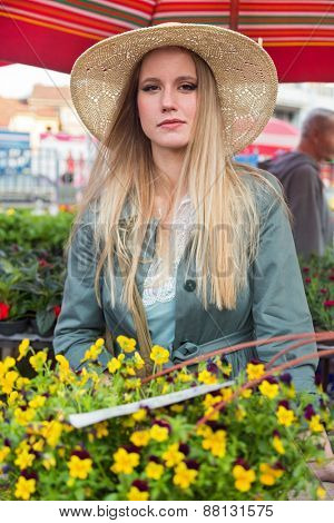 Attractive blonde woman with straw hat posing on flower marketplace.