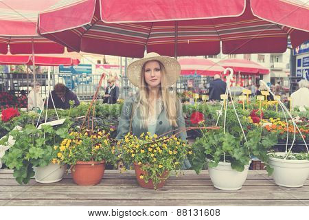Attractive blonde girl with straw hat posing on flower marketplace. Post processed with vintage filter.