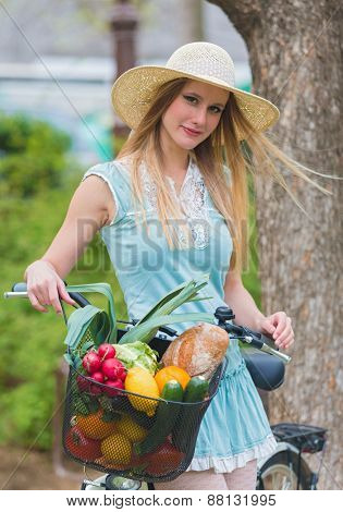 Attractive blonde womanwith straw hat standing in the park and posing next to bike with basket full of groceries.