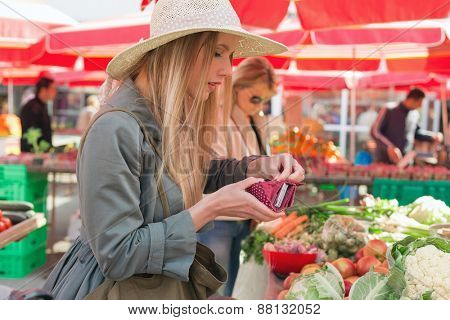 Attractive blonde girl with straw hat posing on flower marketplace.