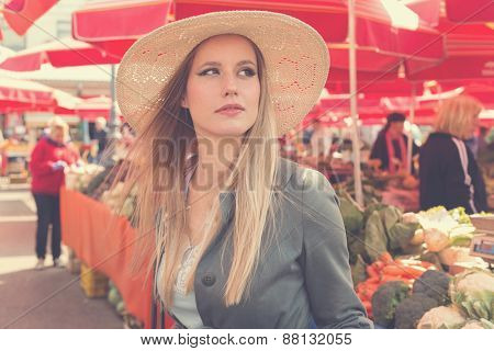 Portrait of attractive blonde woman with straw hat on Marketplace. Post processed with vintage filter.