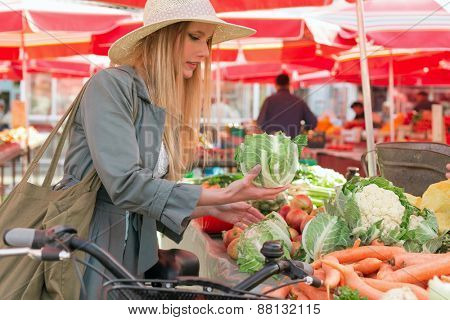 Attractive blonde girl with straw hat buying vegetables on  marketplace.