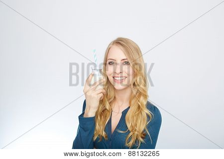 pretty woman holds glass of delicious and pasteurized milk