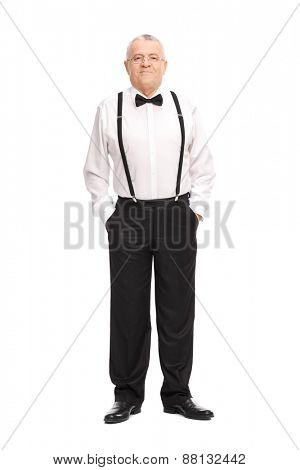 Full length portrait of an elegant cheerful senior standing with his hands in his pockets and looking at the camera