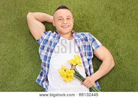 Handsome young man lying on green grass and holding a bunch of flowers