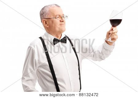Classy senior gentleman looking at a glass full of red wine isolated on white background