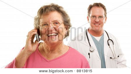 Happy Senior Woman Using Cell Phone With Male Doctor Behind