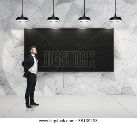 Young Successful Businessman Is Standing In Front Of The Chalkboard In The Concrete Room With Four B