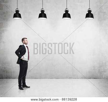 Young Successful Businessman Is Standing In The Concrete Room With Four Black Lamps.