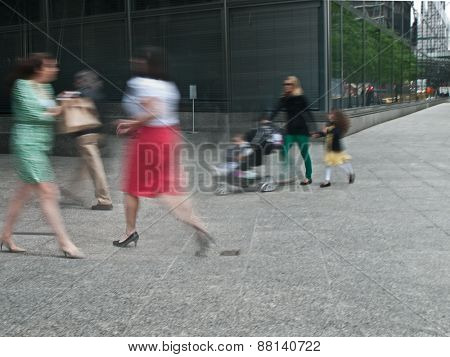 young female parent with stroller rushing on the street in intentional motion blur, business people walking by