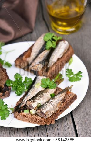 Appetizer Bread With Sprats On White Plate