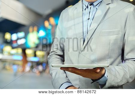 Handsome Young Man In Shopping Mall Using Mobile Tablet