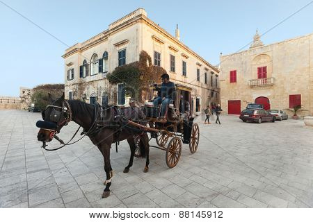 MDINA, MALTA - JANUARY 12, 2015: Tourists being toured by horse carriage around the old city streets