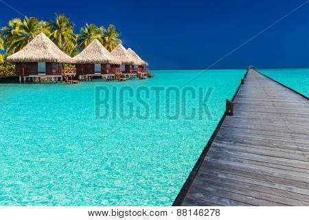 Long wodden jetty extended into azure water of lagoon with villas over the water