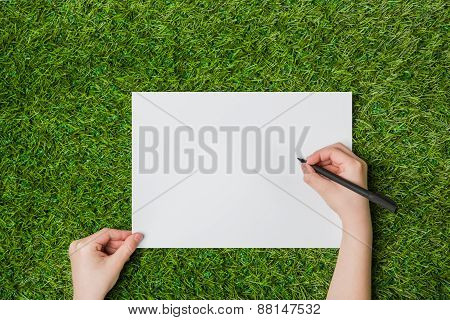 Writing on blank sheet of paper over grass close up