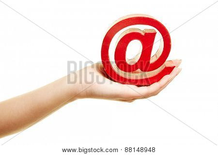Hand holding a big red at sign as symbol for email and internet