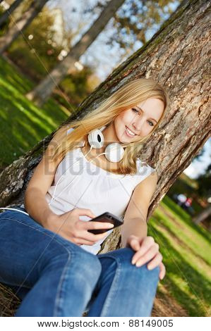 Young blonde woman sitting with smartphone and headphones in summer in a park