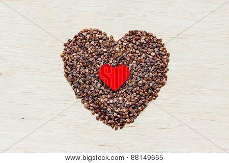 Buckwheat Groats Heart Shaped On Wooden Surface.