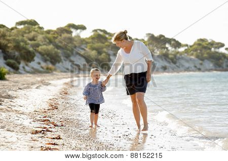 Happy Mother Holding Hand Of Sweet Blond Little Daughter Walking Together On Sand At Beach Sea Shore