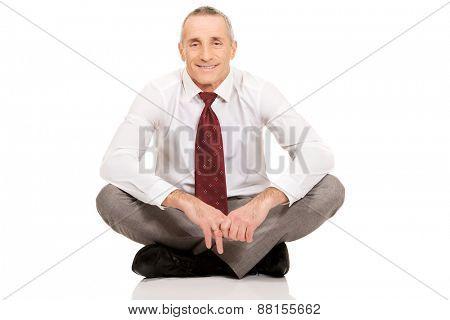 Happy businessman sitting cross-legged on the floor.