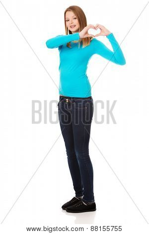 Teenage woman making heart shape with her hands
