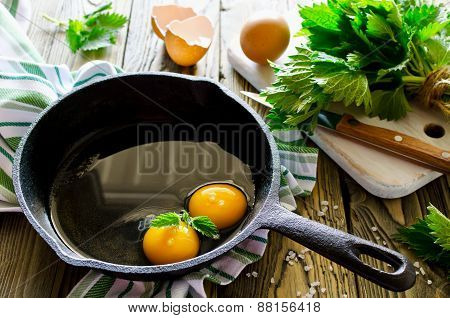 Scrambled Eggs With Nettles In The Pan On Wooden Table